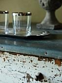 Tablett und Gläser auf Vintage Kommode mit abgeblätterter Lackierung und metallverkleideter Deckplatte