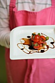 A person serving strawberry and tomato tartar with balsamic vinegar