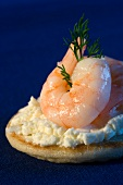 A blini topped with cream cheese and prawns