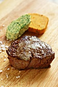 Beef steak with herbs and pepper butter on a wooden board