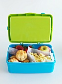 A lunch box filled with mini muffins, fruit and popcorn