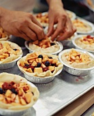 Hands Filling Nectarine Blueberry Croustades Before Baking