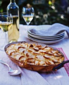 Rustic Potato Gratin on an Outdoor Table; White Wine
