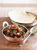 Chickpea curry with aubergines and spinach served with unleavened bread