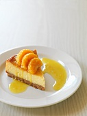 A slice of cheese cake with mandarins