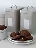 Chocolate biscuits with peanuts and storage tins in the background