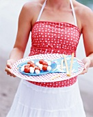 A woman serving mozzarella and tomato on sticks with grissini for a picnic