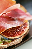 A slice of bread topped with raw ham and fresh figs (close-up)