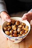 Hands holding a bowl of peeled and roasted chestnuts