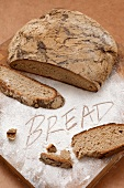 Country bread, sliced and the word BREAD written in flour