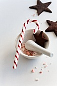 A candy cane in a mortar with chocolate star-shaped biscuits
