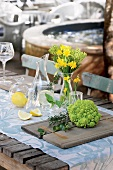 Table set with table runner, bouquet of flowers, Romanesco broccoli and lemons