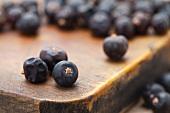 Juniper berries on chopping board (close-up)