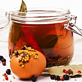 Pickled eggs, preserved in brine and spices, in a jar and in front of it