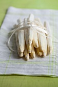 Peeled white asparagus with peel on a kitchen towel