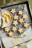 Freshly Baked Star Shaped Cookies on a Cooling Rack; Bowl of Frosting