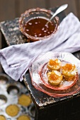 Three Mini Cakes with Candied Citrus Syrup on Top; On Stacked Antique Pink Plates; Bowl of Syrup; Cakes in Pan