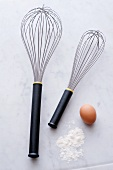 Two whisks, eggs and flour