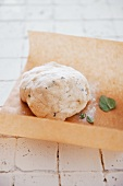 Pizza dough with herbs on a piece of baking paper