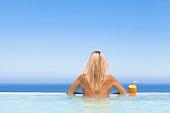 Frau mit Ananascocktail im Pool