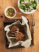 Lamb rack with a chilli and mint sauce and salad (seen from above)