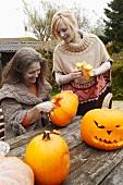 A mother and daughter cutting pumpkins in a garden