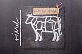 Gezeichnetes Rind und Etikett mit Bezeichnung auf einer Schiefertafel