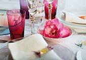 Gedecke und farbige Trinkgläser neben Blumendeko
