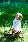 Little girl holding large basket full of fresh produce