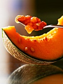 Melon and almond jam on a spoon above a slice of melon