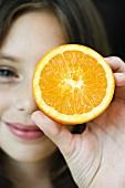 Mädchen hält Orange vor das Auge