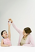 Mädchen greift nach Kirsche in der Hand der Mutter