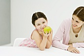 Little girl sitting at table with mother, hand under chin, holding apple, smiling at camera