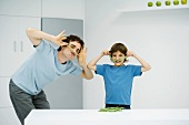 Man and boy in kitchen playing with food, smiling at camera