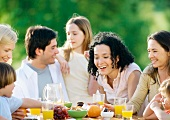 Family sitting around table outdoors