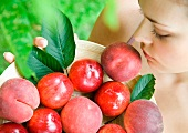 Woman holding bowl of peaches and nectarines