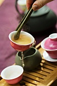Tea cup held with tea tongs, pouring out first brew into tea tray