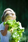 Little girl holding up chard to her face