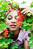 Teenage girl in red currant bush