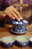 Hand placing lid on tea cup