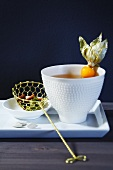 A cup of tea with a physalis and a tea strainer with a cinnamon stick and cardamom