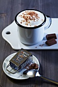 A cafe latte with milk foam and grated chocolate with a mini grater