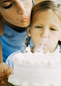 Mother helping daughter blow out birthday candles