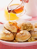 Aebleskiver (apple-filled Danish pastries) being drizzled with maple syrup