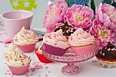 Desserts in bunten Förmchen auf Kuchenschale und Blumendeko