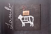 Gezeichnetes Lamm und Etikett mit englischer Bezeichnung auf einer Schiefertafel