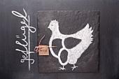 Gezeichnetes Huhn und Etikett mit Bezeichnung auf einer Schiefertafel
