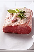 A piece of roast beef with herbs and garlic cloves