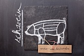 Gezeichnetes Schwein und Etikett mit Bezeichnung auf einer Schiefertafel
