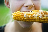 A person eating grilled corn cob